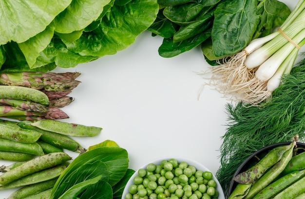 Pois verts, gousses dans un bol et une casserole d'épinards, d'oseille, d'aneth, de laitue, d'asperges, d'oignons verts à plat sur un mur blanc