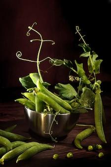 Pois verts en gousses et avec des feuilles sur fond marron.