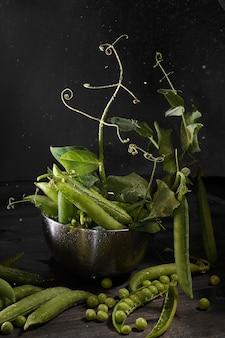 Pois verts en gousses sur fond sombre avec des éclaboussures et des gouttelettes.