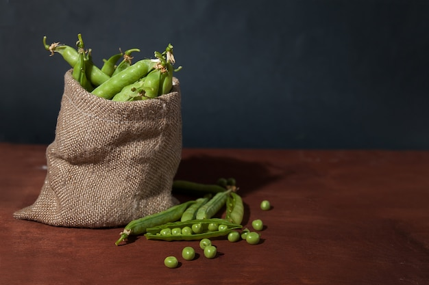Pois verts, gousses et pois dans un sac en toile sur un fond en bois. flatlay.