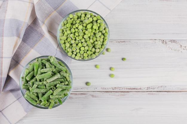 Pois verts et haricots verts coupés dans un bol. concept de préparations maison pour une cuisson rapide. concept de nourriture végétarienne saine. vue de dessus