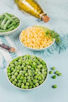 Pois verts, maïs sucré et haricots verts coupés dans un bol. concept de préparations maison pour une cuisson rapide. concept de nourriture végétarienne saine