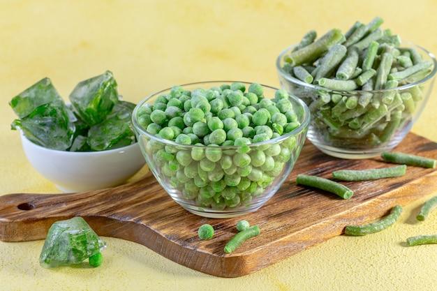 Pois verts surgelés, haricots verts, glaçons avec persil frais sur une planche de bois