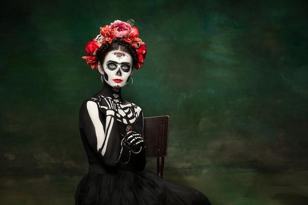 Poison jeune fille comme la mort de santa muerte saint ou le crâne de sucre avec le maquillage lumineux