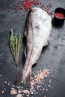 Poisson d'aiglefin cru sans tête. fond noir.