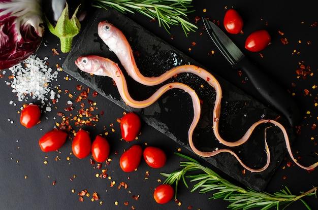 Poisson d'anguille avec légumes et romarin sur une ardoise noire sur fond sombre