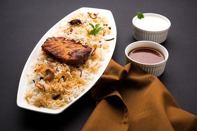 Poisson biryani authentique servi dans une assiette blanche sur fond blanc, mise au point sélective