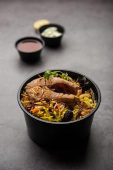 Poisson biryani ou pulao de style restaurant emballé pour la livraison à domicile dans une boîte ou un conteneur en plastique avec raita et salan