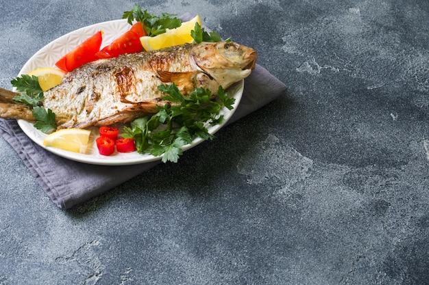 Poisson carpe au four avec des légumes et des épices sur une assiette sur une table sombre avec une copie de l'espace.