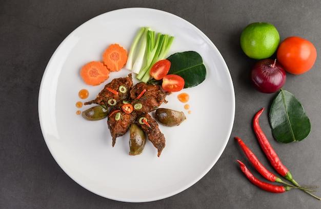 Poisson-chat frit épicé sur plaque blanche, cuisine thaïlandaise.