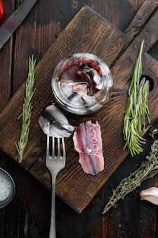 Poisson en conserve d'anchois dans une boîte de conserve de fruits de mer, sur une planche à découper en bois, sur une vieille table en bois sombre avec des herbes et des ingrédients, vue de dessus à plat