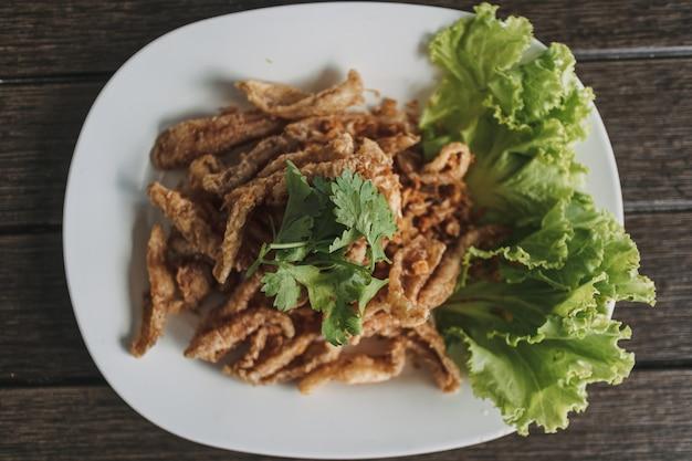 Poisson croustillant thaïlandais servi dans un plat blanc décoré de légumes
