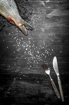 Poisson cru avec un couteau et une fourchette sur une table en bois noire.