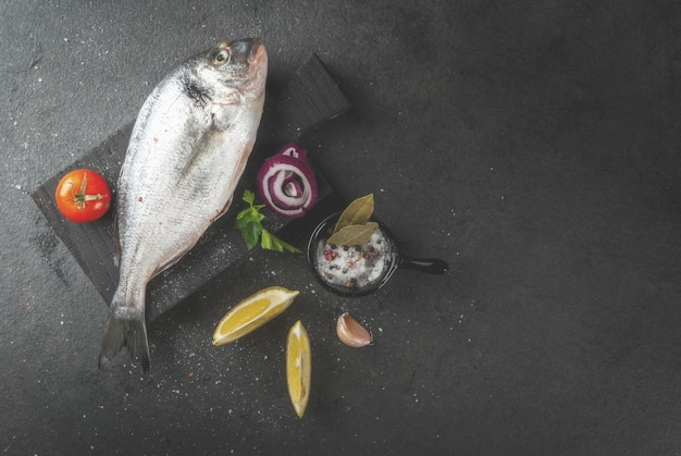 Poisson cru cru bio dorado, dorade avec des ingrédients pour la cuisson du citron, tomates, oignons, sel, poivre, laurier, légumes verts, huile. sur une vieille planche à découper en bois, sur une table en pierre noire vue de dessus copie espace
