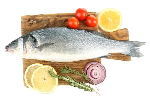 Poisson cru frais sur une planche à découper et ingrédients alimentaires isolés sur blanc