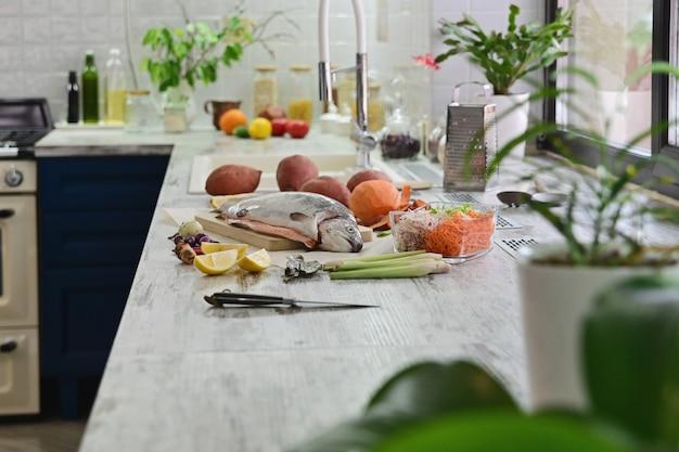 Poisson cru pour cuisiner avec des légumes sur la table de la cuisine.