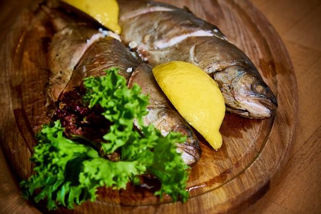 Poisson cuit au citron et salade sur une planche de bois.