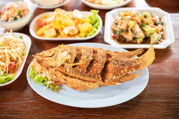 Poisson cuit avec d'autres délicieux plats thaïlandais sur une table en bois