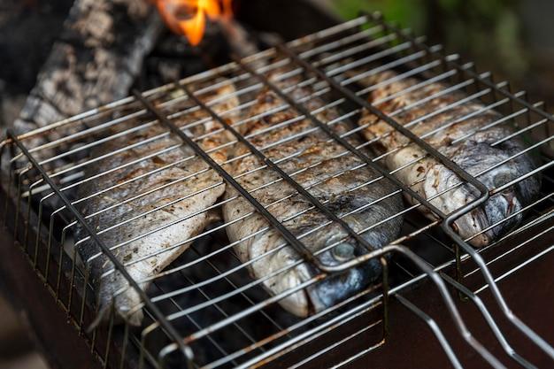Le poisson dorado est frit sur le gril. pique-nique en pleine nature. fermer.