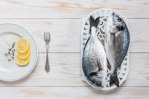 Poisson dorado frais aux épices, huile d'olive, ail et assaisonnement sur un plat blanc sur tableau blanc.