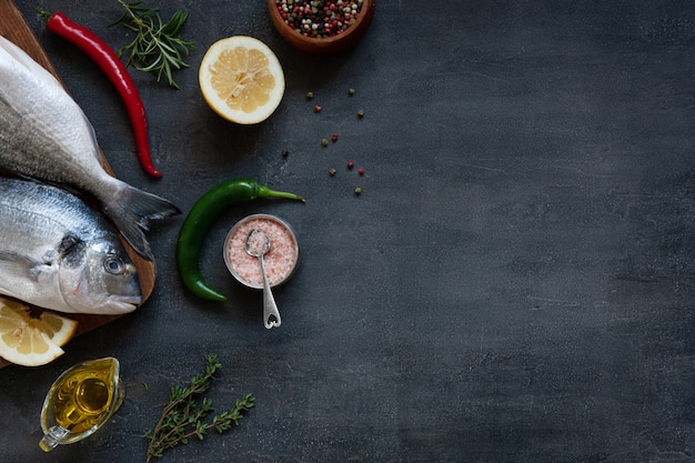 Poisson dorado frais, épices et huile d'olive sur une planche à découper en bois sur un tableau noir. vue de dessus, espace de copie.