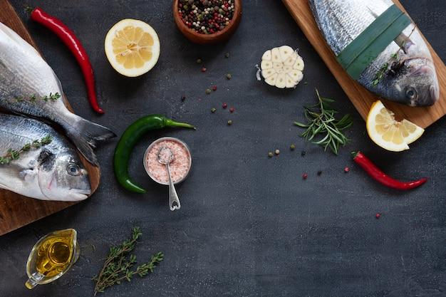 Poisson dorado frais, épices et huile d'olive sur des planches à découper en bois sur un tableau noir. vue de dessus, espace de copie.