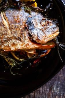 Poisson dorado frit avec gros plan de citron et de romarin et de sel de mer. alimentation saine. prise de vue verticale