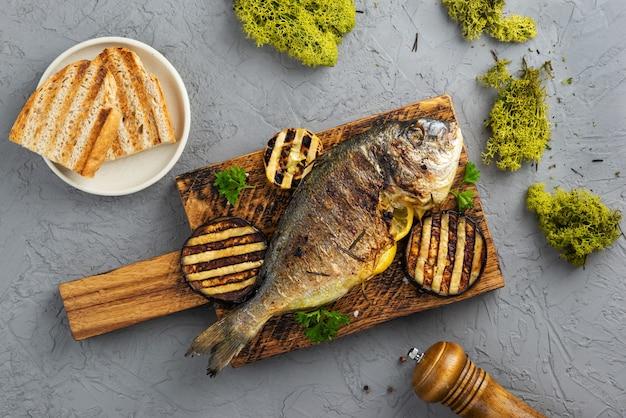 Poisson dorado grillé au citron et aubergine sur une planche en bois