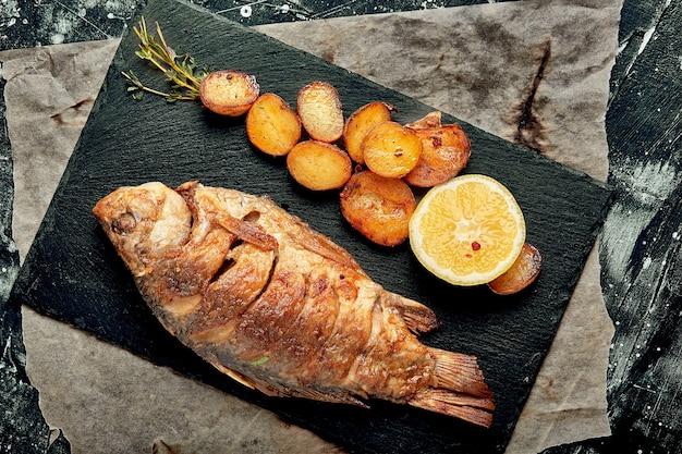 Poisson entier grillé servi avec pommes de terre au four, citron et sauce. vue de dessus.