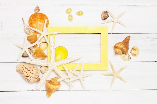 Poisson étoile, coquillages et cadre en bois jaune sur fond blanc en bois.