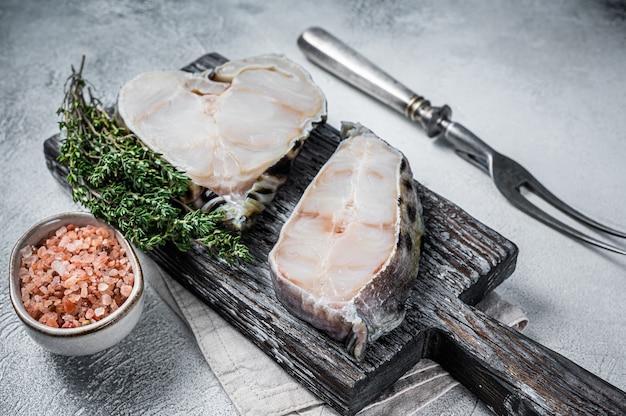 Poisson de filet de loup de mer cru steak sur une planche à découper en bois. fond blanc. vue de dessus.