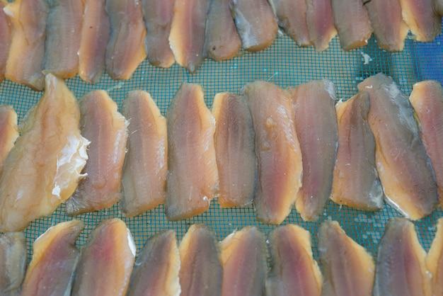 Poisson frais sur filet en plastique sous la lumière du soleil pour faire du poisson séché