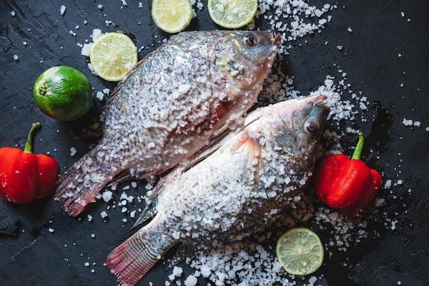 Poisson frais de tilapia au sel et assaisonnement pour la cuisson.