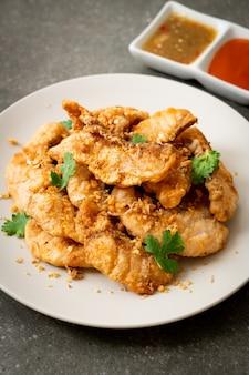 Poisson frit à l'ail sur assiette