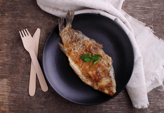 Poisson frit (carpe) sur une assiette noire décorée de persil