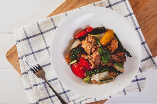 Poisson frit avec des légumes à la sauce au poivre noir