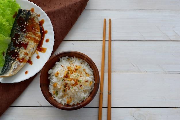 Poisson frit en plaque blanche, baguette, serviette, riz sur le dessus en bois pour l'espace