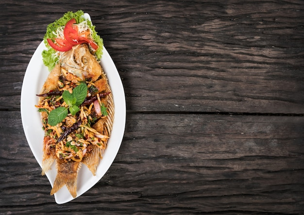 Poisson frit avec salade épicée en assiette sur table en bois