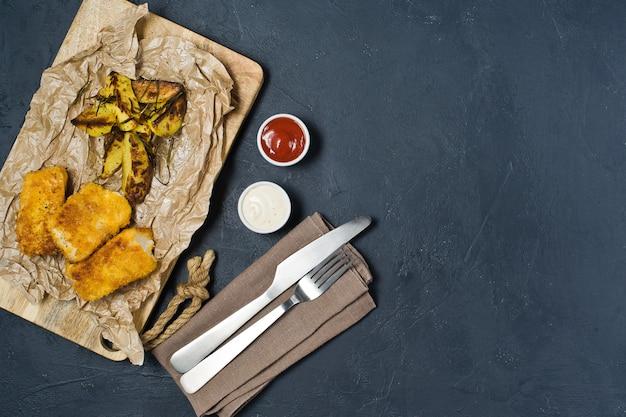 Poisson et frites traditionnels anglais sur une planche à découper en bois.