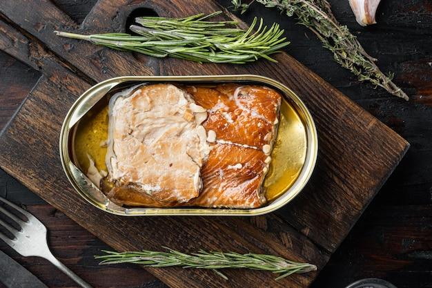Poisson fumé en conserve de saumon sauvage de l'alaska, sur une planche à découper en bois, sur un vieux fond de table en bois foncé avec des herbes et des ingrédients, vue de dessus à plat