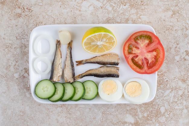 Poisson fumé, légumes et œufs sur plaque blanche