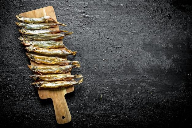 Poisson fumé sur une planche à découper en bois