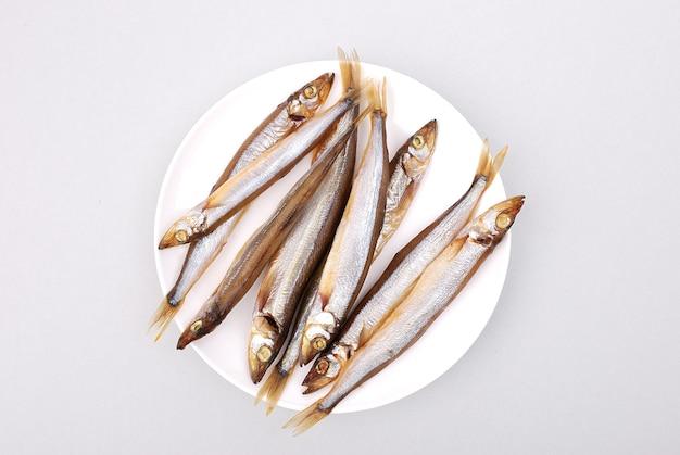Poisson fumé avec rondelles d'oignons sur une assiette