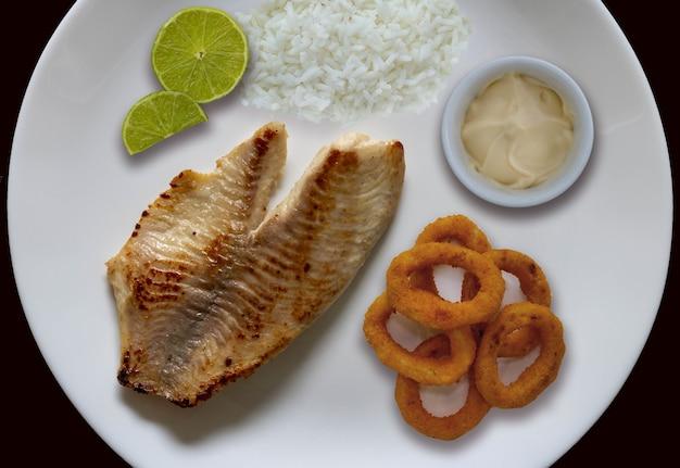 Poisson grillé riz rondelles d'oignon citron et sauce sur le côté