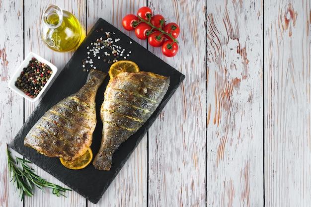Poisson grillé avec rôti au citron, romarin, tomates, huile d'olive et épices sur plat en ardoise noire, sur fond de bois blanc. vue de dessus, mise à plat avec espace de copie.