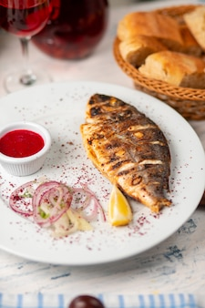 Poisson grillé rôti servi avec des herbes, salade au citron, à l'oignon et à la sauce tomate rouge.