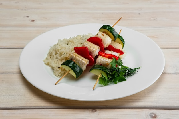 Poisson et légumes grillés sur une brochette de riz bouilli