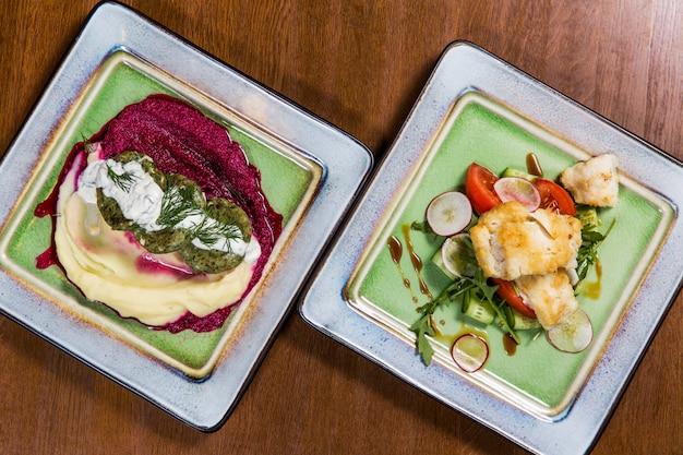 Poisson avec des légumes et des sauces dans des assiettes carrées sur une table en bois dans un restaurant de luxe