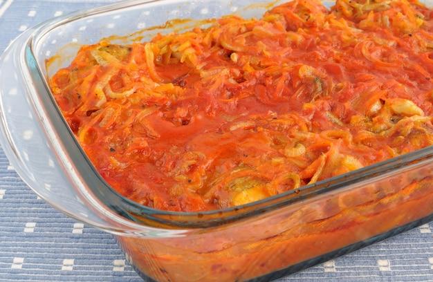 Poisson marin cuit au four avec oignons et carottes à la sauce tomate