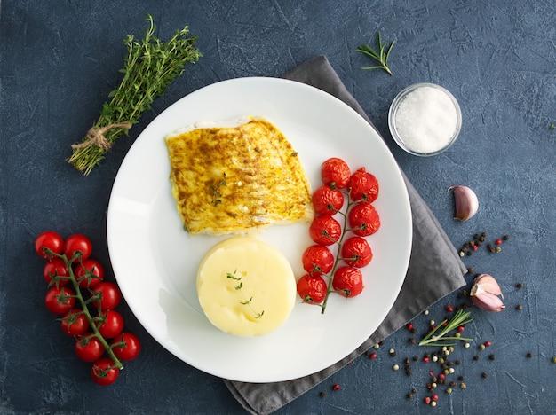 Poisson morue cuite au four avec purée de pommes de terre, tomates, aliments sains diète.